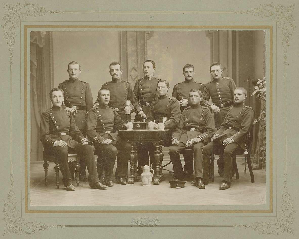 Robert Eugen Orth, Vizefeldwebel, im Kreis seiner Kameraden (zehn Personen) der 1. Kompanie, teils um einen Tisch sitzend, teils im Atelier stehend, Bild 1