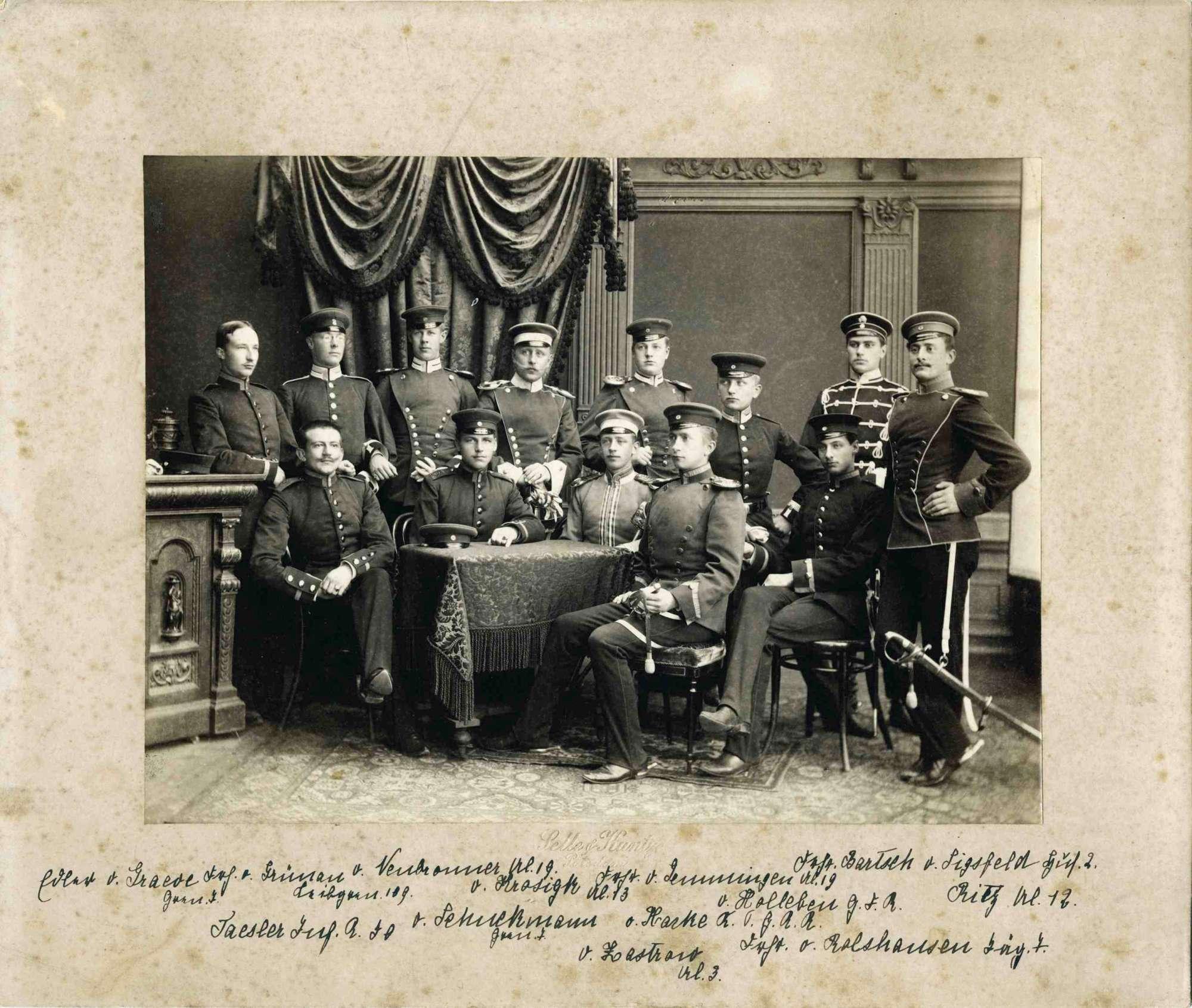 Offiziere (dreizehn Personen) verschiedener Regimenter, Erinnerung des abgebildeten Freiherrn von Gemmingen, Oberst, in Fotoatelier, teils stehend oder um einen Tisch sitzend, Bild 1