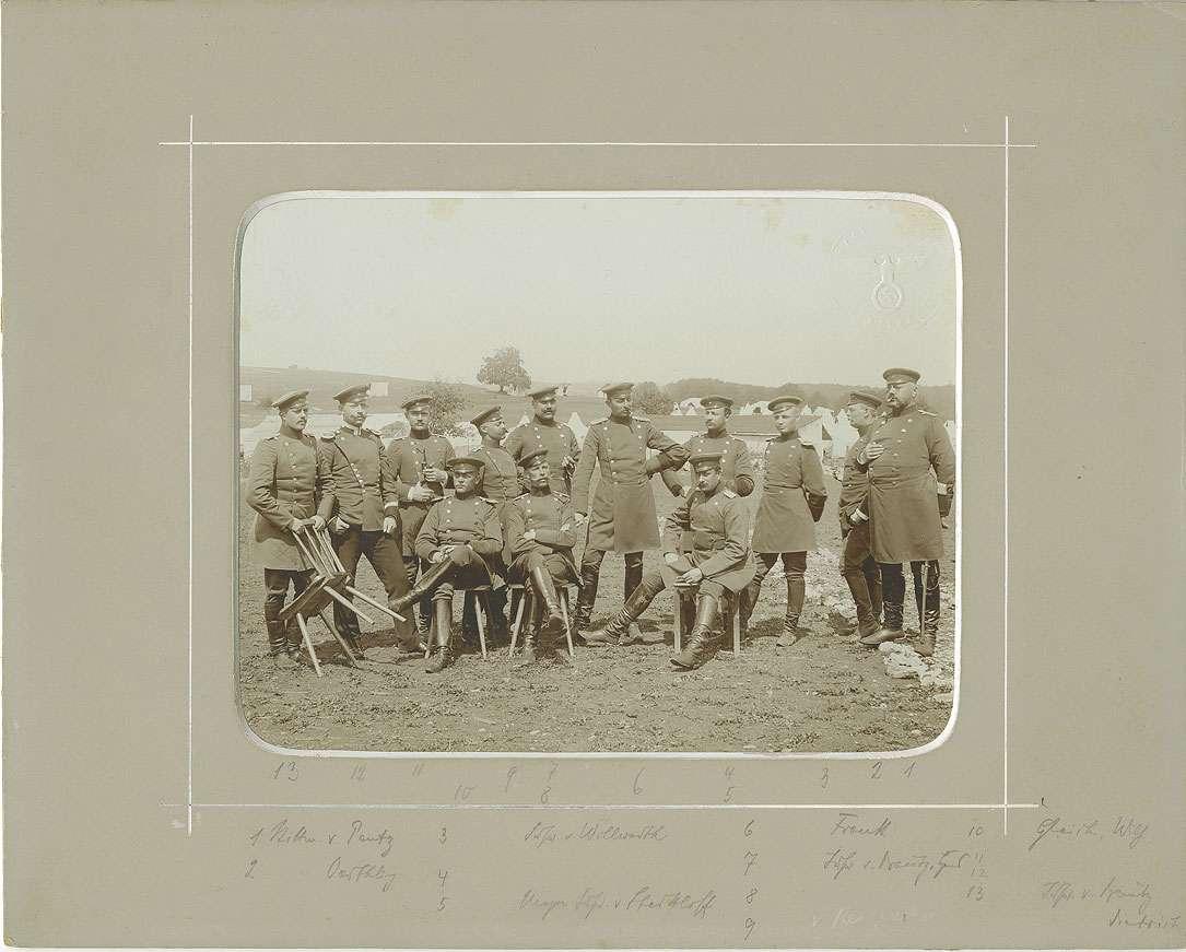 Offiziere (dreizehn Personen) bei den Manövertagen auf Truppenübungsplatz Münsingen, unter ihnen Freiherr Friedrich von Reitzenstein, späterer Oberstleutnant, teils stehend oder sitzend, im Hintergrund Zeltlager, Bild 1