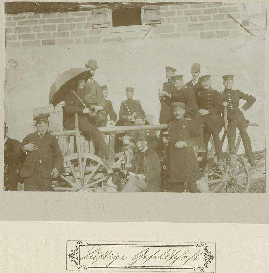 Lustige Gesellschaft im Rahmen der Musterung in Betzingen: Gruppe von Uniformierten und Zivilisten auf und neben einem Leiterwagen, ein aufgespannter Regenschirm, Bild 1