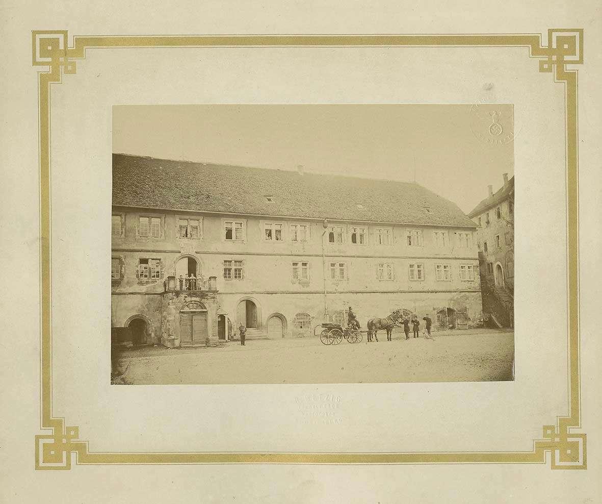Innenhof Festung Hohenasperg mit Wohnung des Kommandeurs, auf Balkon Kinder, darunter Wachhabender, daneben offene Kutsche mit Zivilist und drei Soldaten, Bild 1