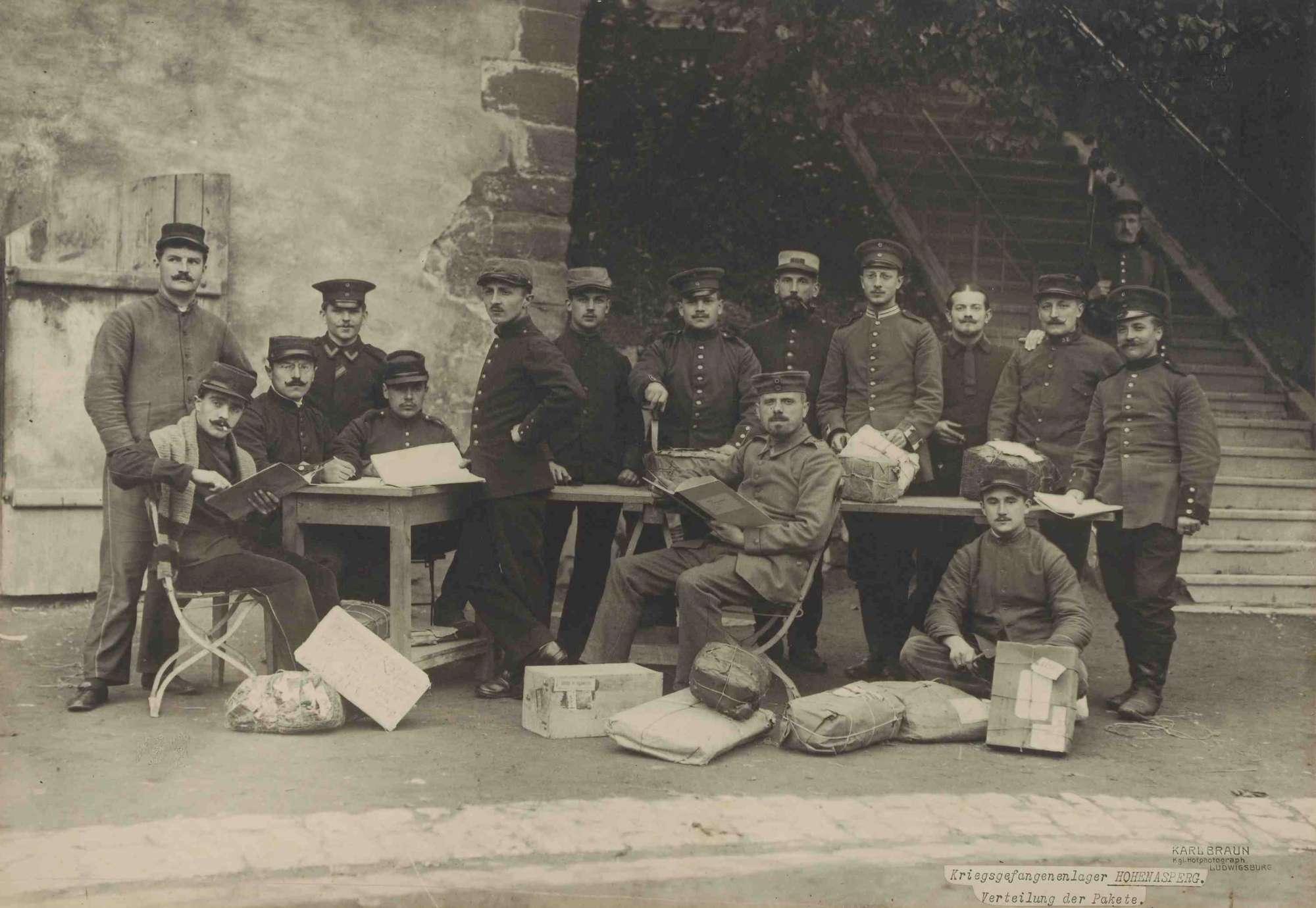 Fünfzehn Kriegsgefangene, teils stehend, teils sitzend an Tischen beim Verteilen von Paketen, Bild 1