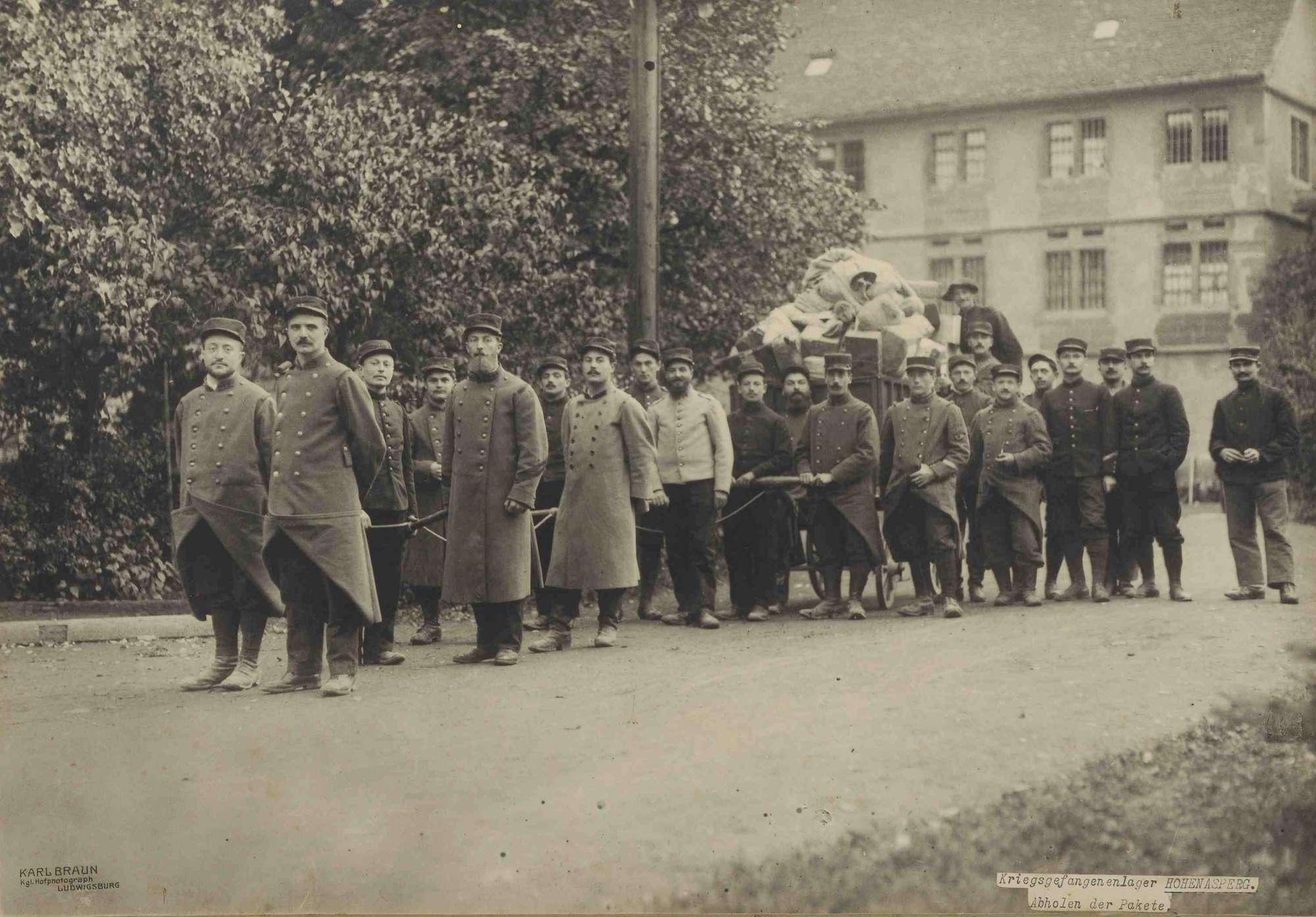Zweiundzwanzig Kriegsgefangene im Kriegsgefangenenlager Hohenasperg vor einem gezogenen Wagen mit Säcken und Paketen, im Hintergrund Innenhofgebäude, Bild 1