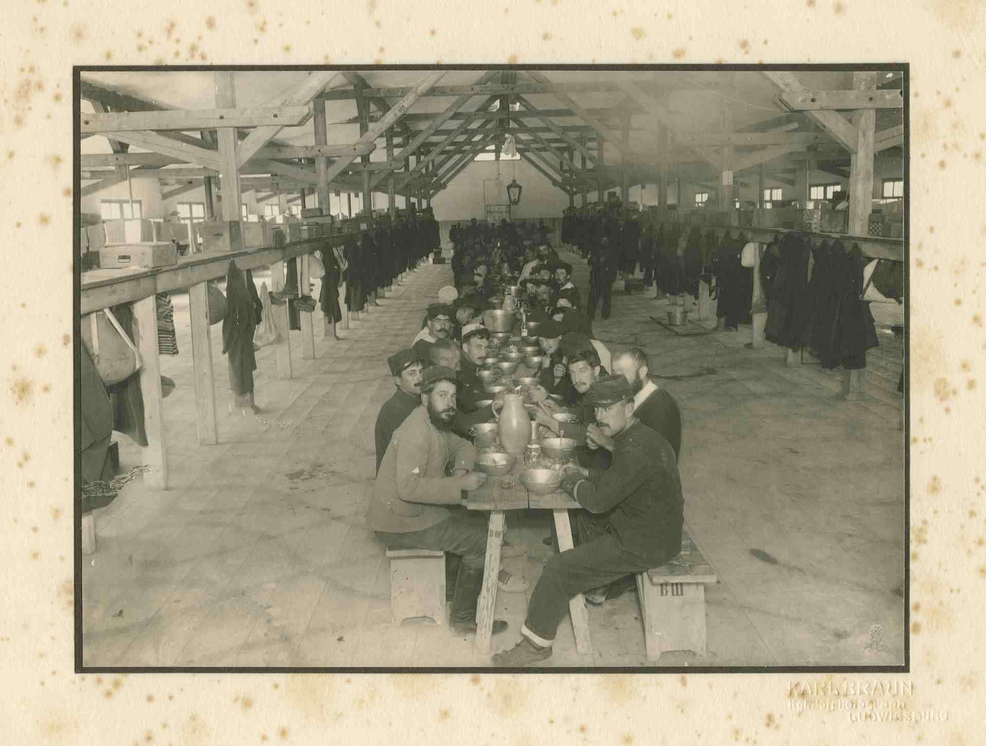 Kriegsgefangene beim Mittagessen an langem Tisch in Baracke, Kriegsgefangenenlager Ludwigsburg-Eglosheim, Bild 1