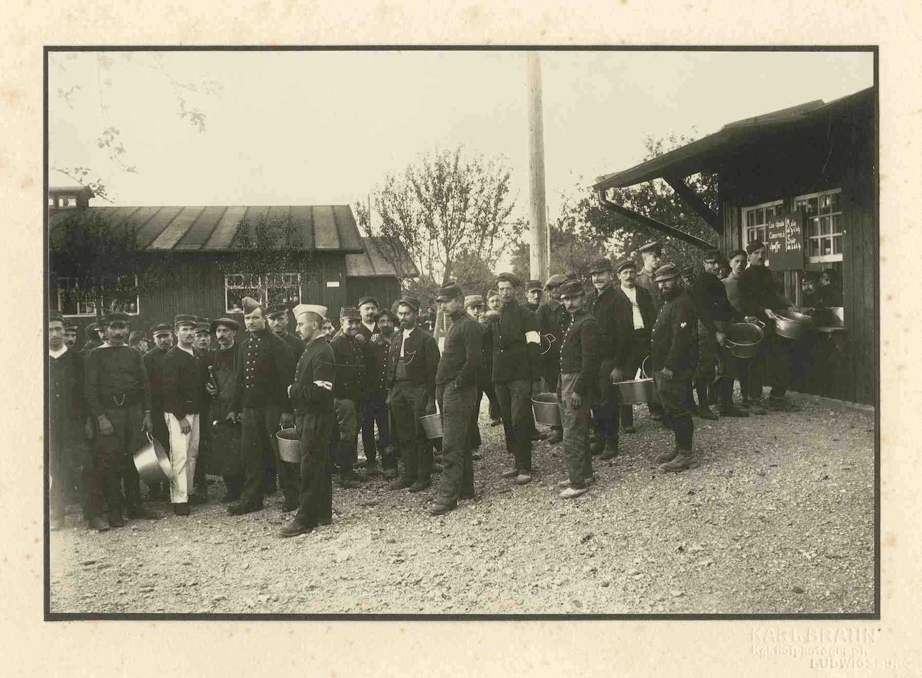 Gruppe von Kriegsgefangenen mit Metallschüsseln vor Essensausgabestelle im Kriegsgefangenenlager Ludwigsburg-Eglosheim, Bild 1