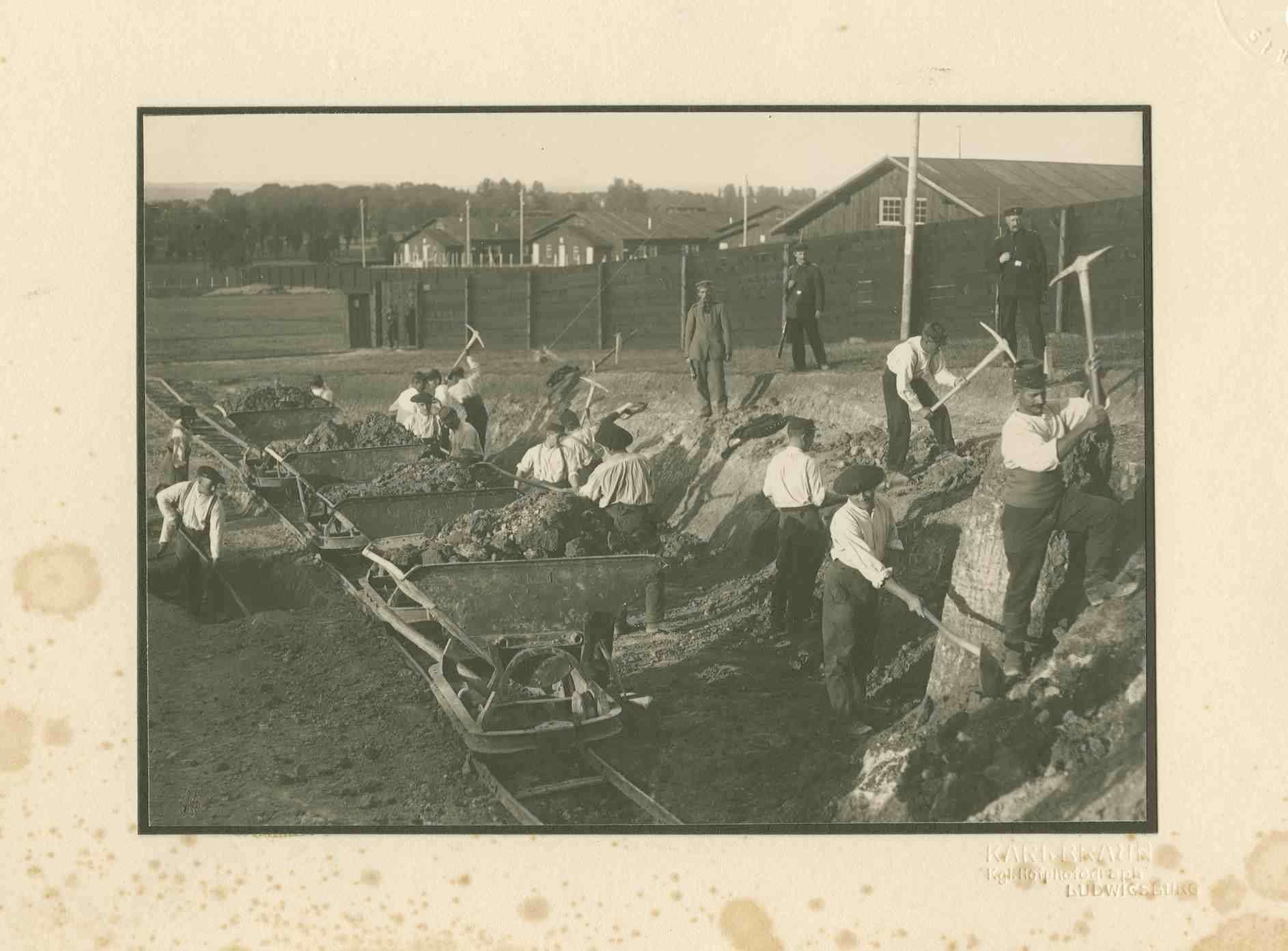 16 Kriegsgefangene mit Spitzhacken und Schaufeln bei Erdarbeiten (Geländebegradigung) im Ausseneinsatz, zwei Wachhabende, Kriegsgefangenenlager Ludwigsburg-Eglosheim, Bild 1