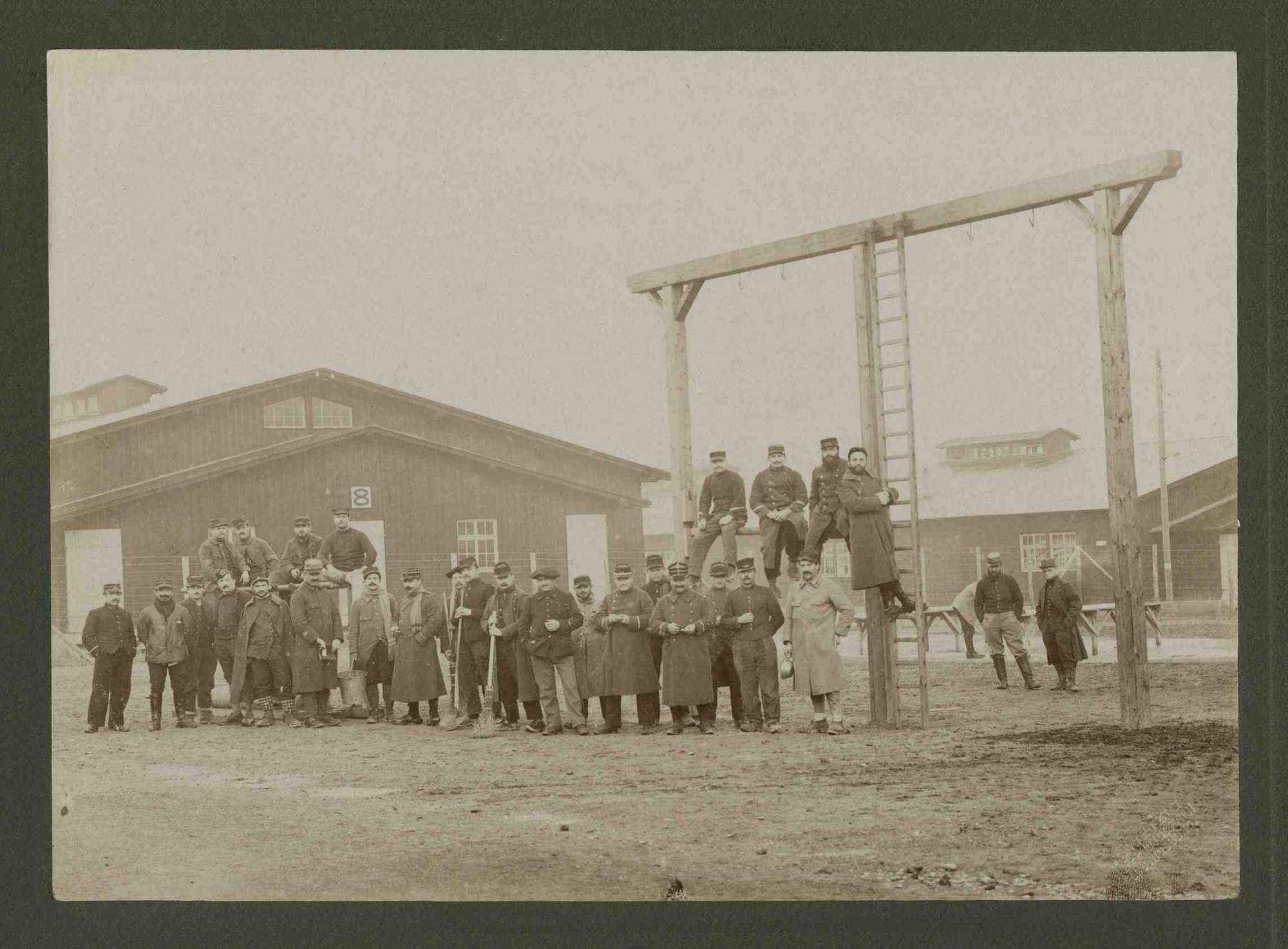 Reinigungstrupp der Kriegsgefangenen, teils stehend teils auf Turngeräten sitzend im Innenhof Kriegsgefangenenlager Ludwigsburg-Eglosheim, Bild 1
