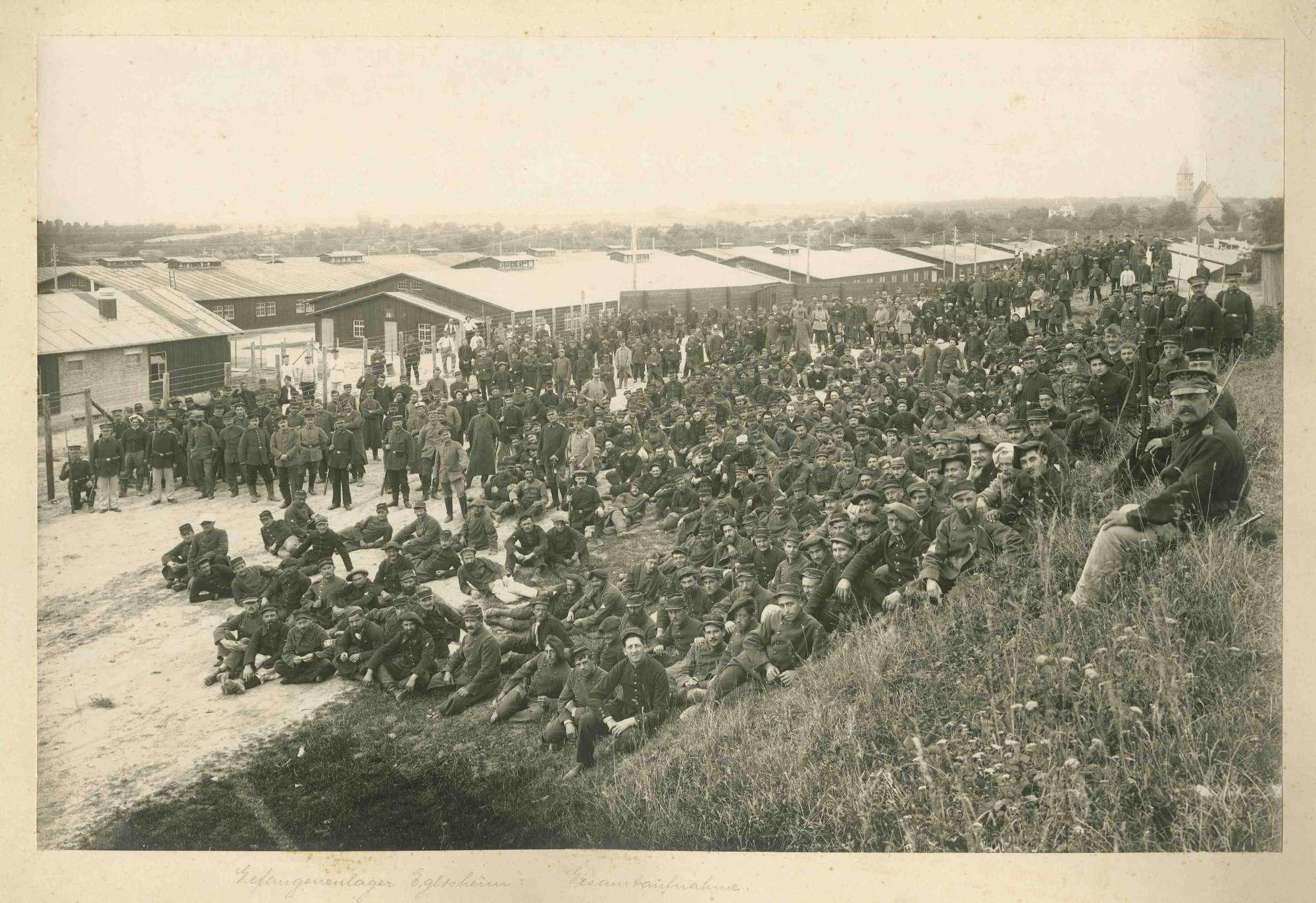 Teilansicht des Kriegsgefangenenlagers Ludwigsburg-Eglosheim mit Versammlung der Kriegsgefangenen, teils stehend, teils sitzend, Wachhabende, im Hintergrund rechts oben Kirche, Bild 1