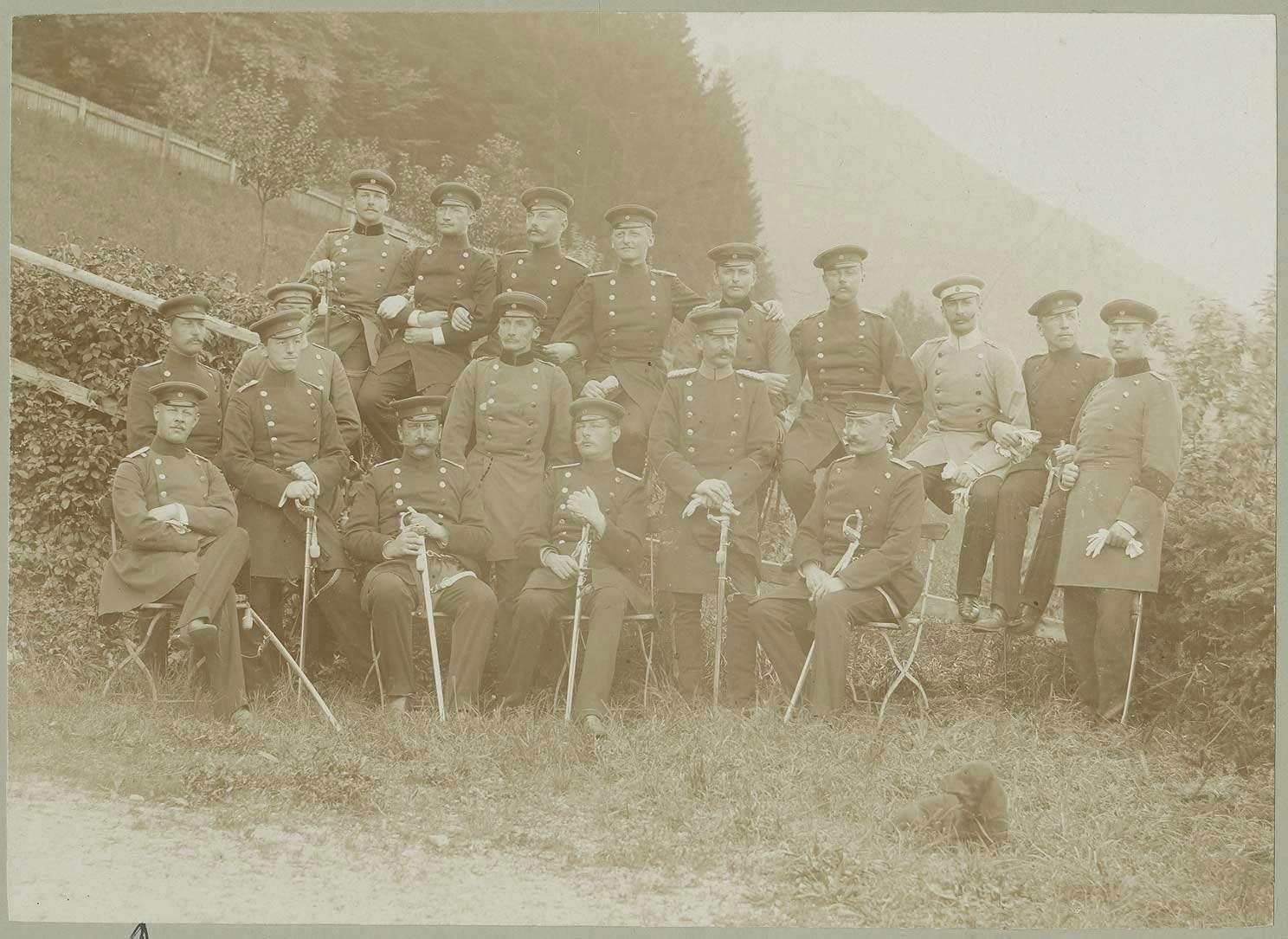 18 Offiziere auf dem Truppenübungsplatz Münsingen, teils stehend, teils sitzend in Uniform, Mützen und Säbeln, Bild 1