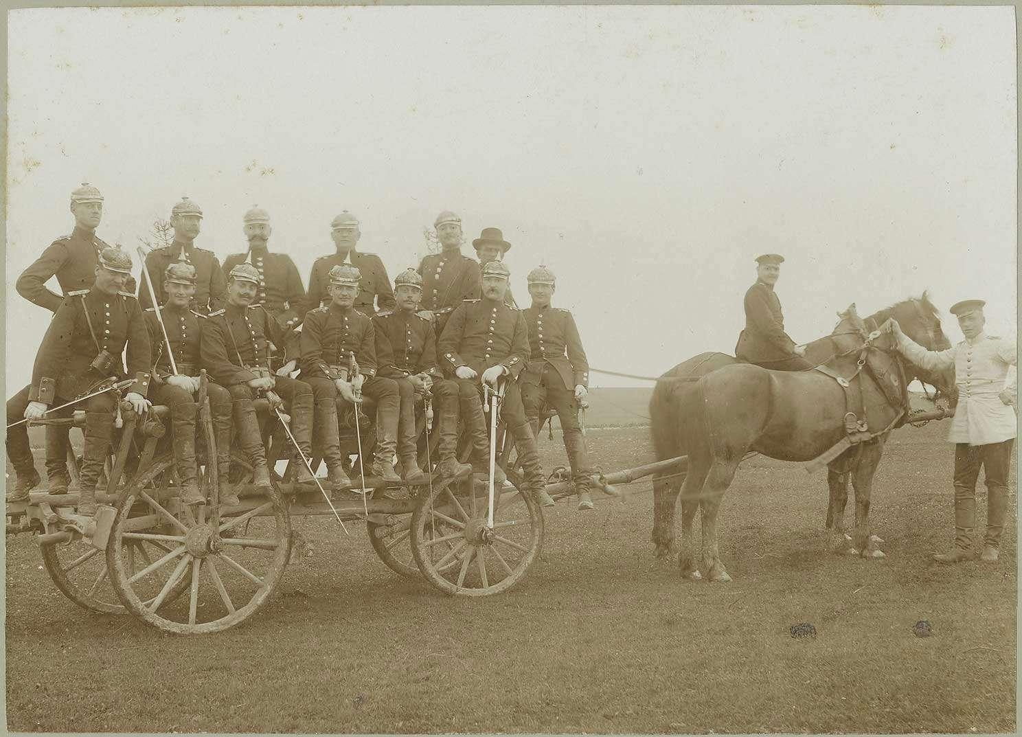 12 Soldaten in Uniform und Pickelhaube, ein Zivilist mit Hut auf Pferdefuhrwerk teils stehend, teils sitzend auf Truppenübungsplatz bei Münsingen, Bild 1