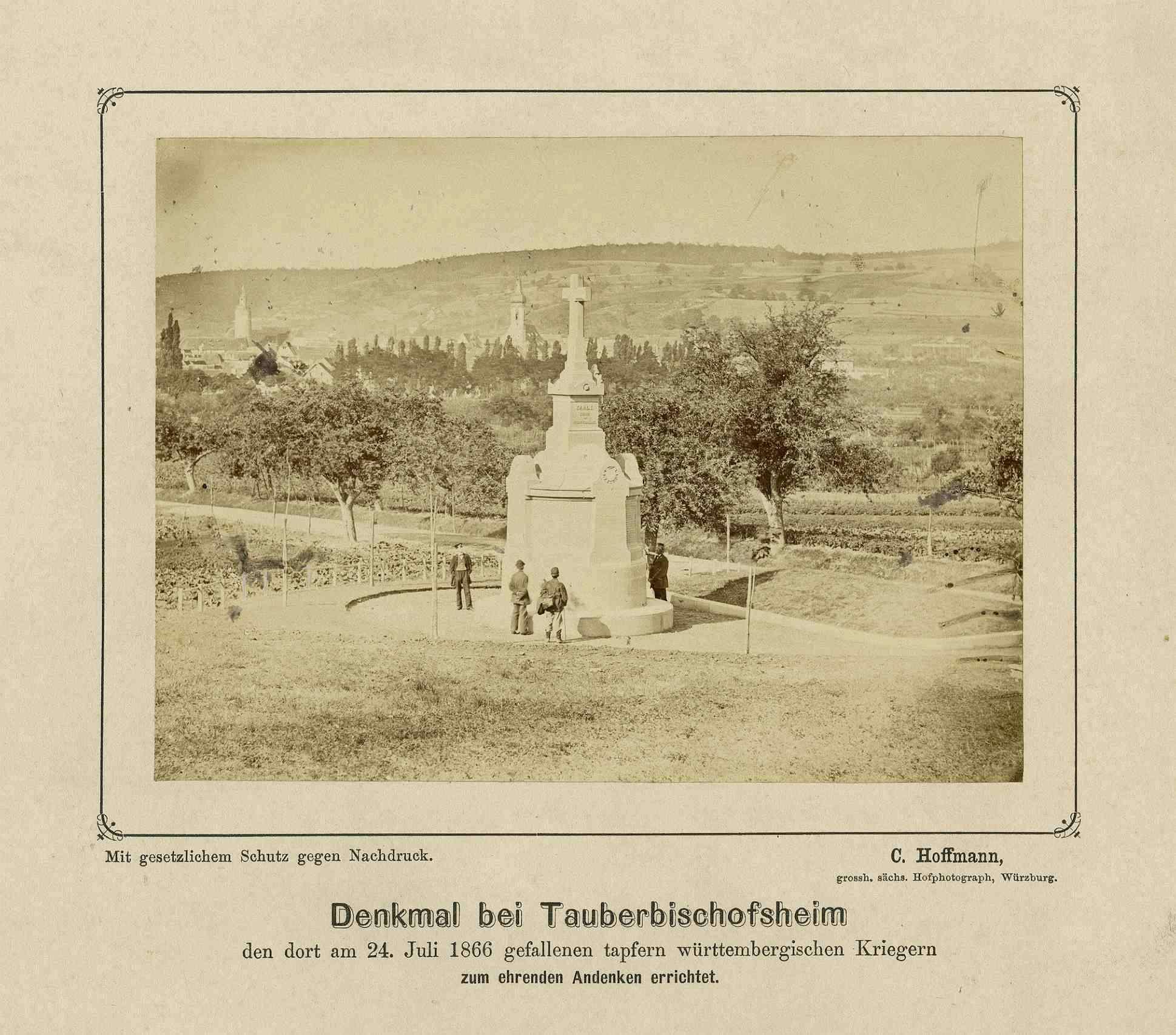 Kriegerdenkmal bei Tauberbischofsheim, vier Zivilisten am Denkmal, im Hintergrund das Stadtbild Tauberbischofsheim, Bild 1