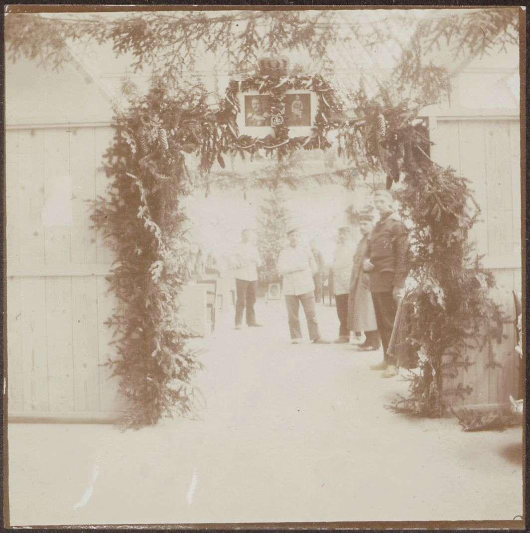Lazarett-Eingang mit Tannenzweigen, darüber Porträts von Hindenburg und Kaiser Wilhelm II., Bild 1