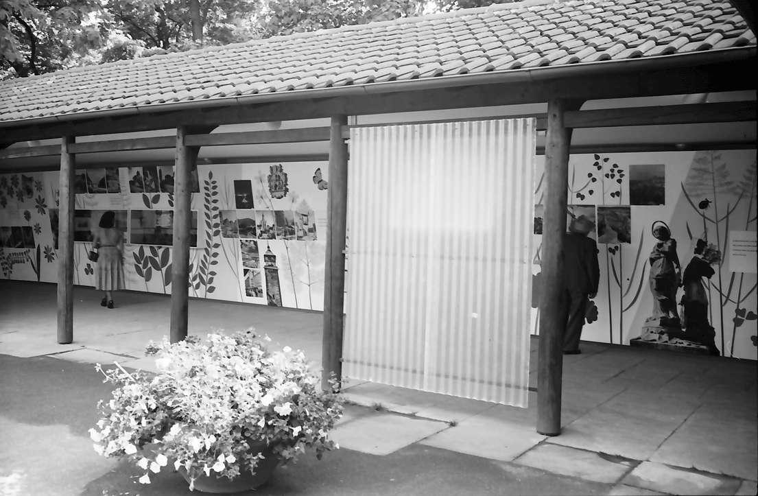 Stuttgart: Landesausstellung, Pavillon des Fremdenverkehrs, Wand mit Bilddarstellungen, Vordergrund Blumenkübel, Bild 1
