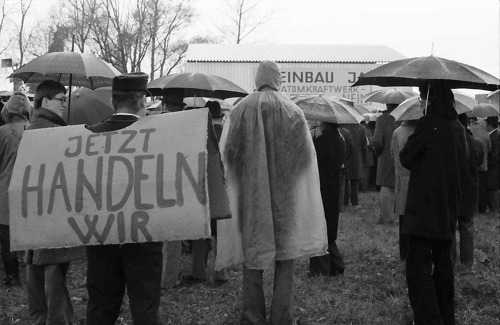 Sasbach: Kundgebung gegen Bleiwerk Marckolsheim und Atomkraftwerk Wyhl; Protestwehrversammlung im Regen mit Plakaten, Bild 1