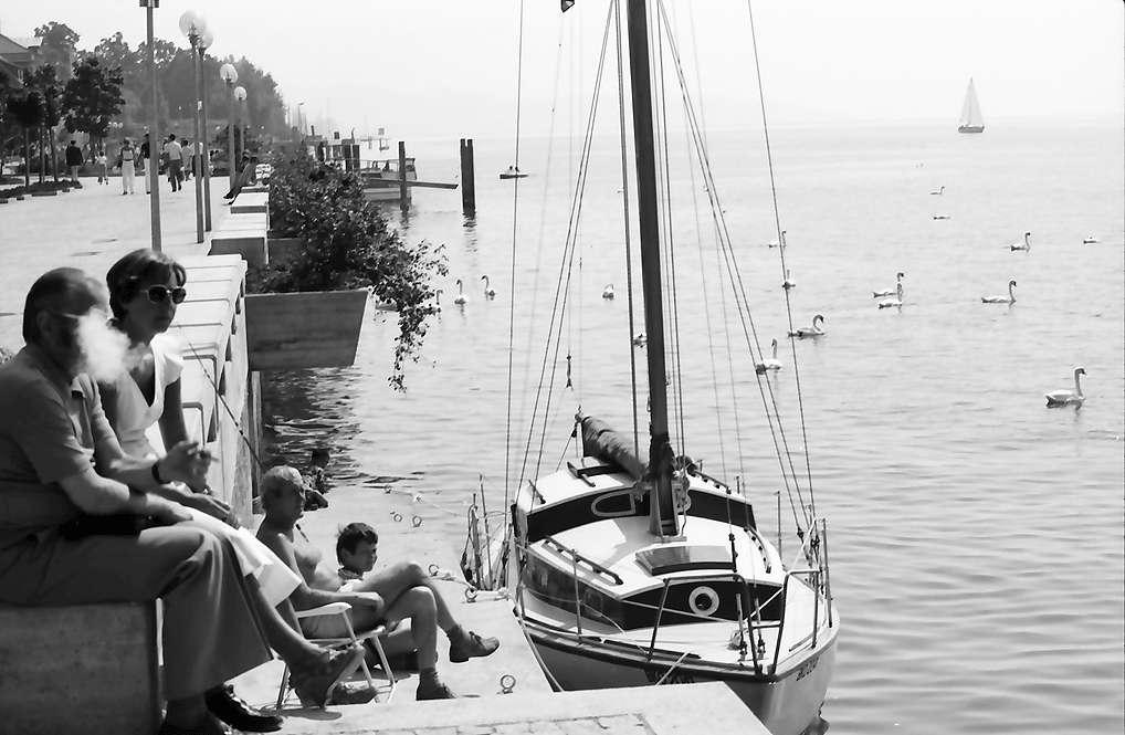 Überlingen: Zwei hocken auf Kante der Seepromenade, mit Boot, Bild 1