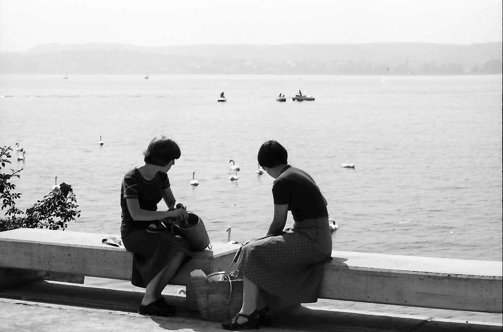 Überlingen: Zwei hocken auf Kante der Seepromenade, zwei Mädchen, Hintergrund See, Bild 1