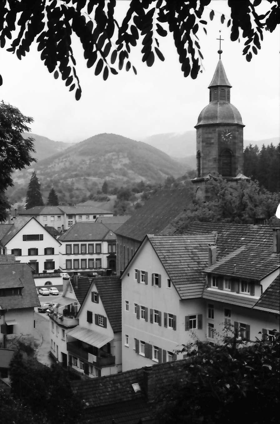 Oppenau: Durchblick durch Wald auf alte Häuser mit Kirchturm, Bild 1