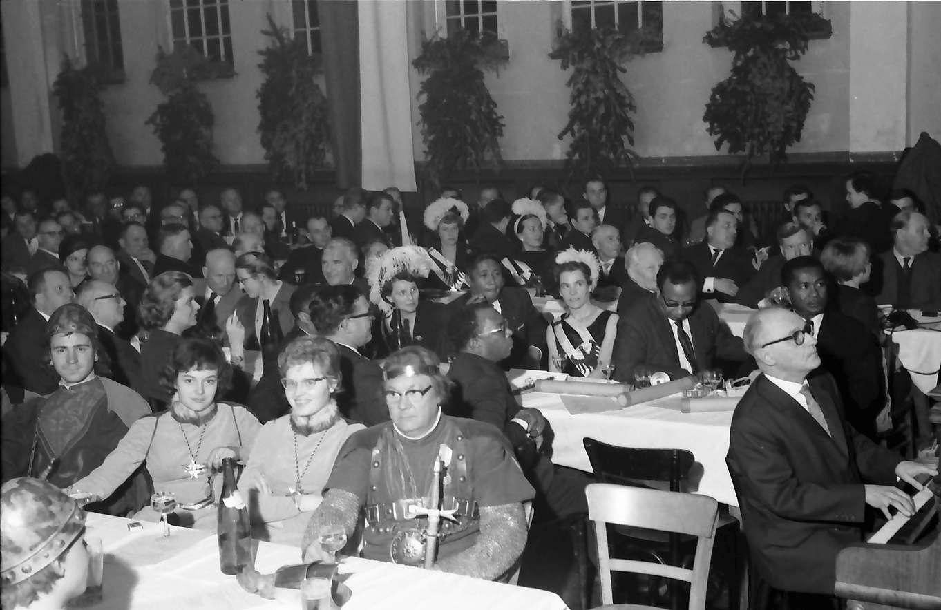 Zähringen: Jahnhalle; fünf Minister aus Madagaskar in Freiburg; Tisch mit Gästen aus Madagaskar; Vordergrund Oberlehrer der Emil-Gött-Schule am Klavier, Bild 1