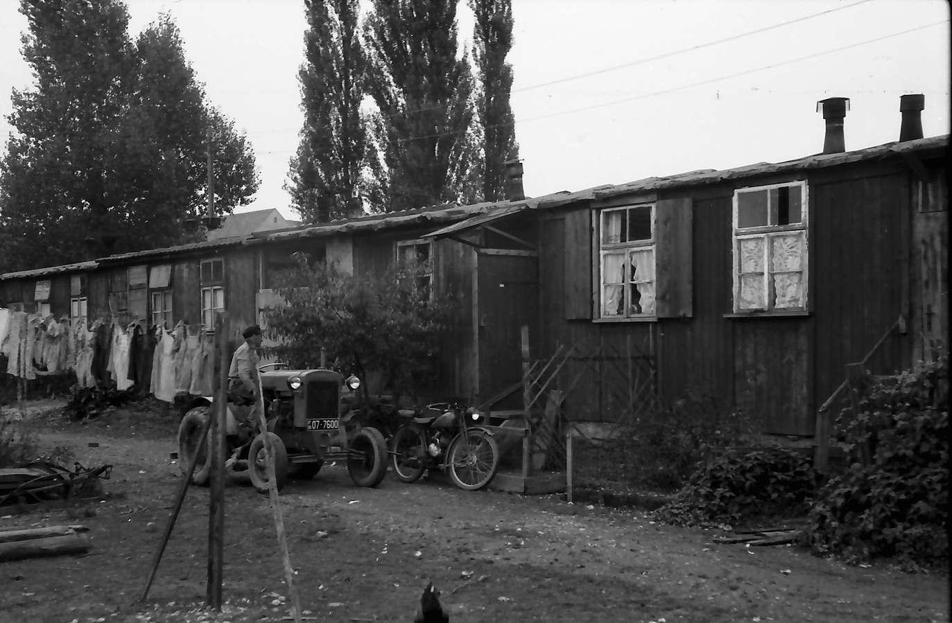 Neuenburg: Elendsbaracke mit Wäsche und Traktor, Bild 1