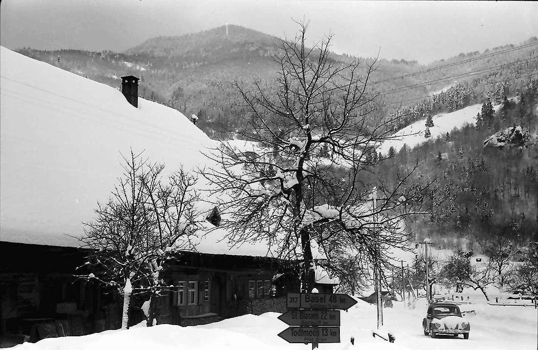 Geschwend: Bauernhaus im Schnee mit Straßenschildern und Autos, Bild 1