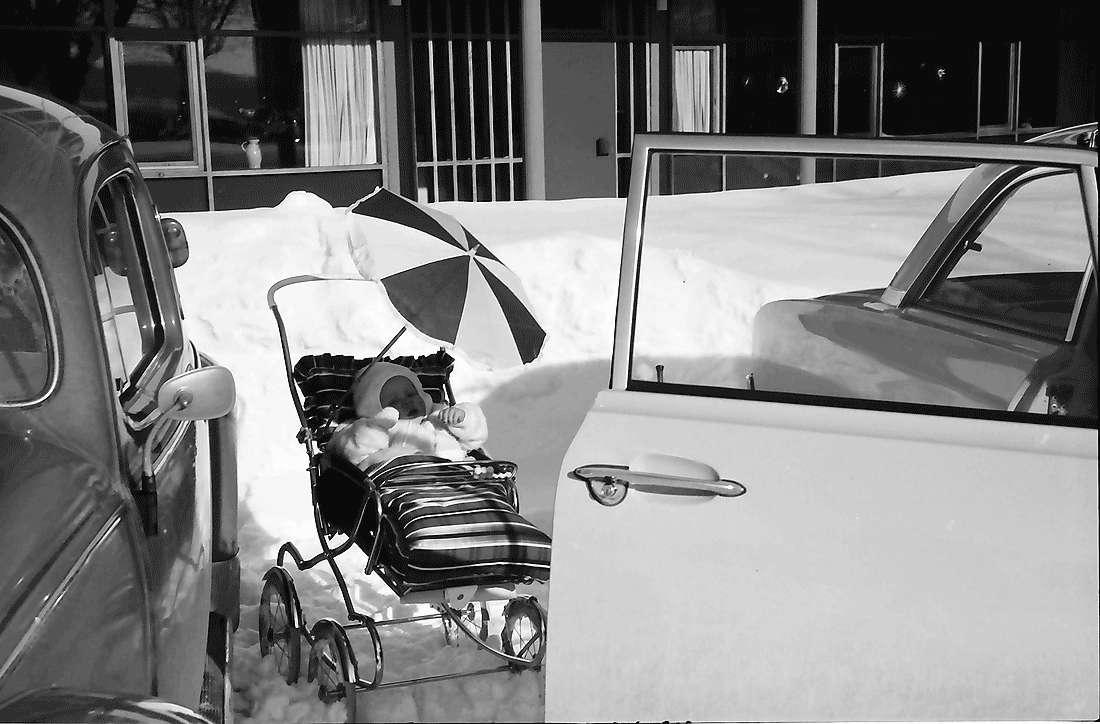 Breitnau: Kind im Kinderwagen; mit Sonnenschirm, zwischen Autos, Bild 1
