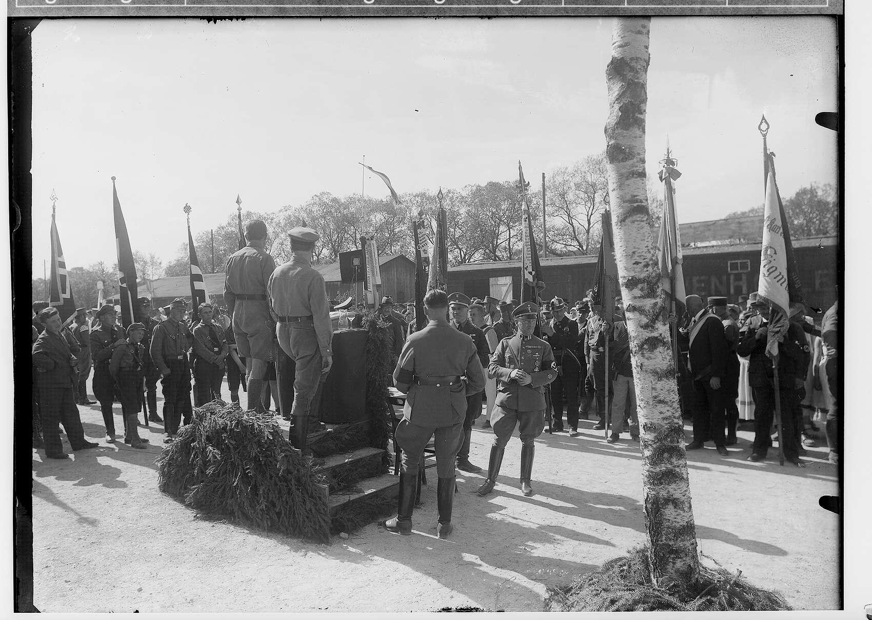 1. Mai-Feier Sigmaringen 1934; Aufnahme des Rednerpults von hinten; zahlreiche Fahnenträger im Hintergrund; rechts vom Rednerpult in Stahlhelmuniform Fürst Friedrich Viktor von Hohenzollern, Bild 1