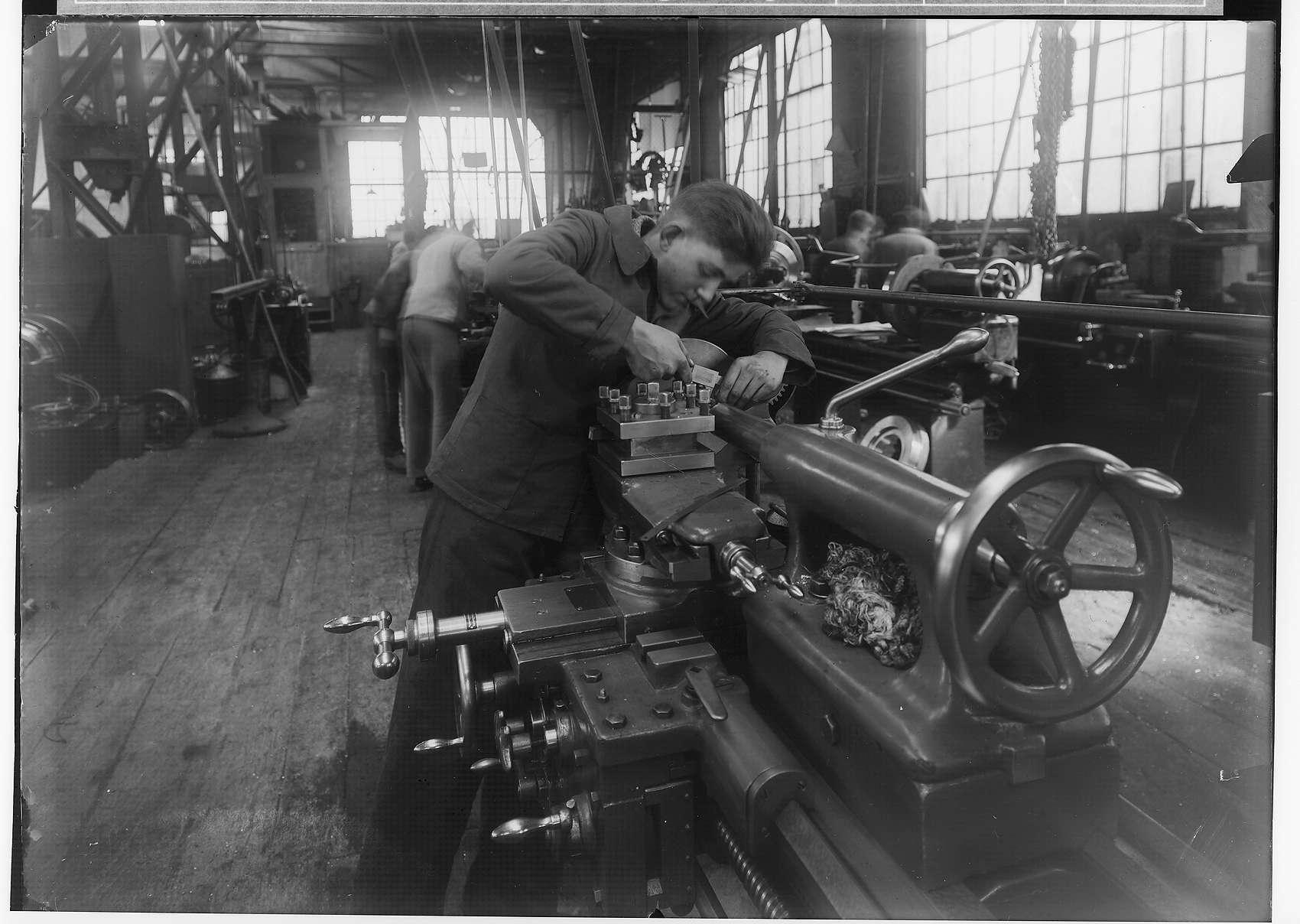 Reichsjugendwettkämpfe - Nettal(?)-Wettkämpfe 1934; Feinmechaniker beim Fräsen in einer Werkshalle Laucherthal; im Hintergrund weitere Personen bei der Arbeit, Bild 1
