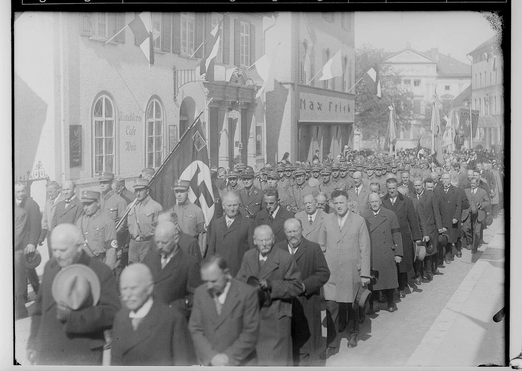 Fidelisfest in Sigmaringen 1934; Prozession in der Antonstraße, am linken Bildrand Cafe Stumpp, im Hintergrund Prinzenpalais; im Mittelpunkt SA-Standarte 40 mit Hakenkreuzfahne, Bild 1