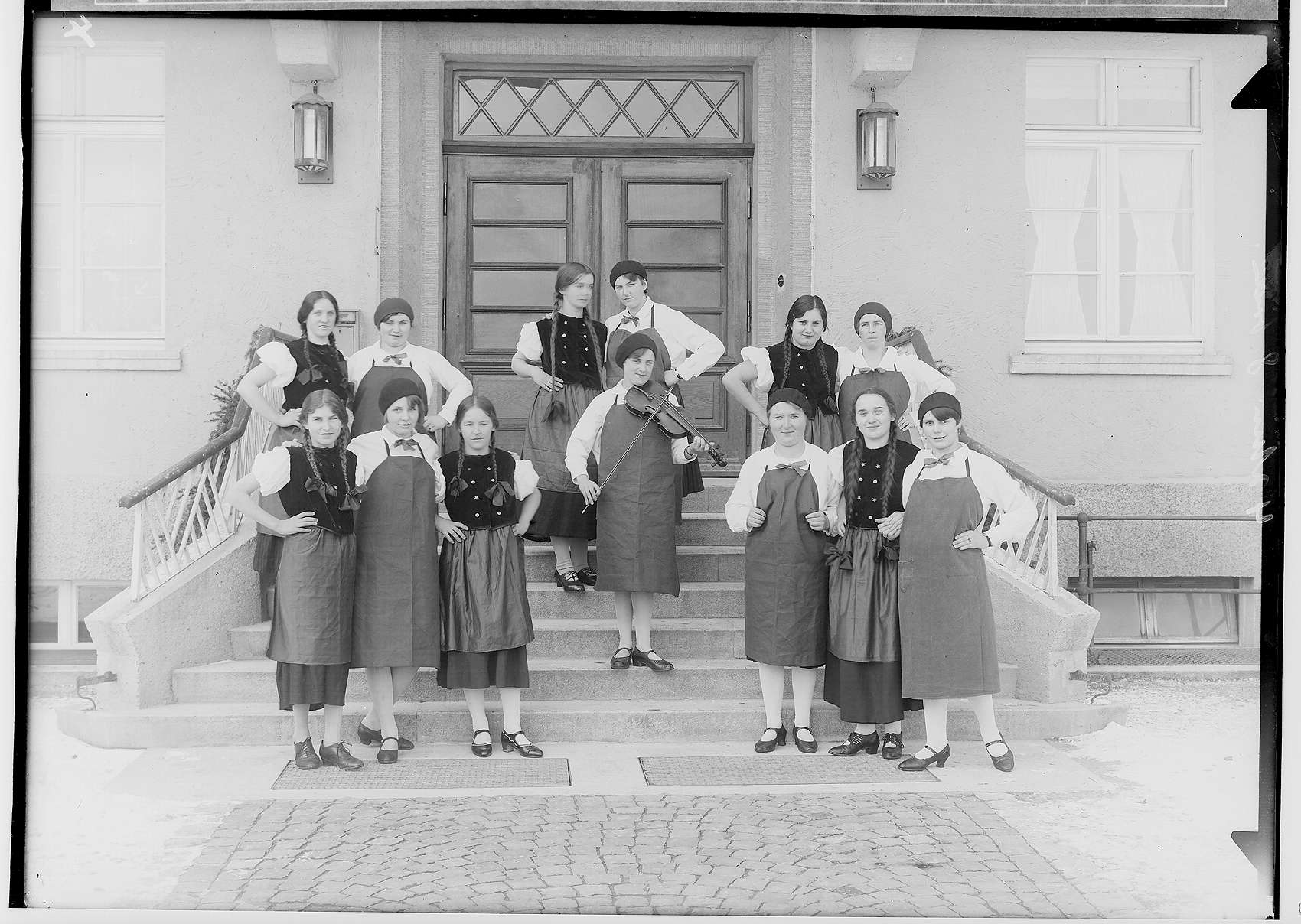 Haushaltungsschule in Gammertingen 1931; Junge Frauen mit Schürzen bei einer Aufführung mit Geigenspielerin auf einer Treppe vor dem Hauseingang, Bild 1