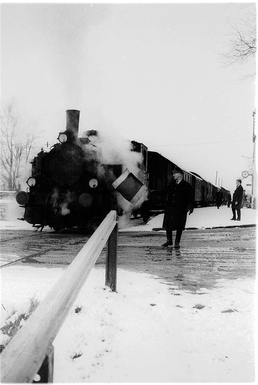 Lok 12, Bahnübergang Landesbahnhof Hechingen, der Stationsschaffner sichert mit der Signalflagge, mit Pfeifen und Läuten startet der Güterzug, Bild 1